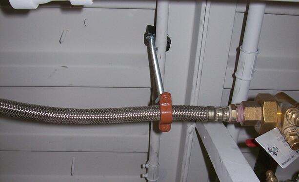 This pipe clamp puts the weight on the flexible hose and its coupling, neither of which are rated to support weight.